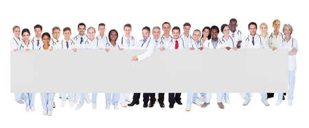 doc: Portrait of multiethnic doctors holding blank banner against white background