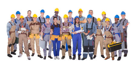 Panoramic shot of confident manual workers standing against white background photo