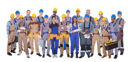 constructor: Toma panor�mica de los trabajadores manuales conf�a en pie contra el fondo blanco