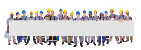 Portrait of multiethnic manual workers holding blank banner against white background Stock Photo
