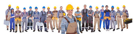 Portrait of happy construction worker with colleagues standing over white background photo