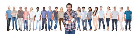 Portrait of confident man in casuals with friends standing against white background photo
