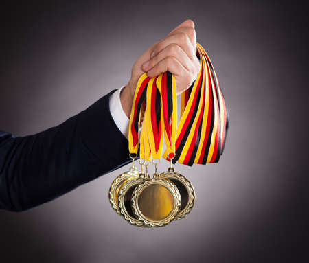 Cropped image of businessman holding gold medals against black background photo