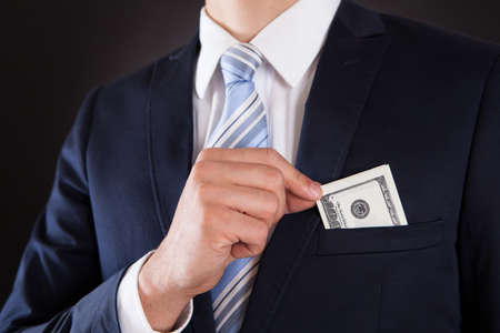 putting money in pocket: Midsection of businessman putting money in pocket against black background