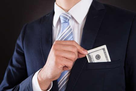 bolsa dinero: Sección media de hombre de negocios de poner dinero en el bolsillo contra el fondo negro