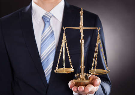 Midsection of businessman holding justice scale against black background