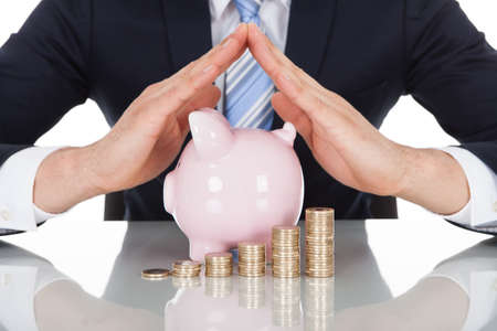 protection hands: Midsection of businessman sheltering coins and piggybank at desk
