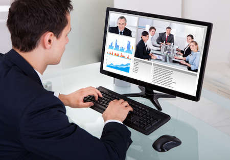 Businessman video conferencing with team on computer at desk in office