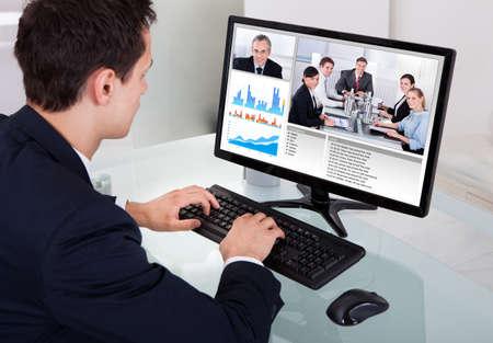 ordinateur bureau: Homme d'affaires vidéoconférence avec l'équipe sur ordinateur au bureau en bureau