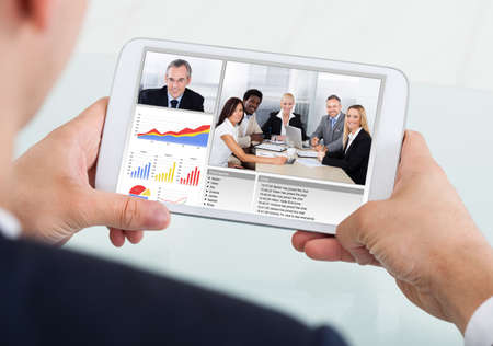 conferencing: Cropped image of businessman video conferencing with team on digital tablet at desk in office