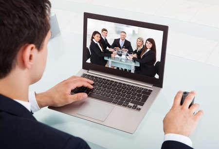 mujeres trabajando: Recorta la imagen de joven empresario de conferencia de v�deo en la computadora port�til en el escritorio en la oficina