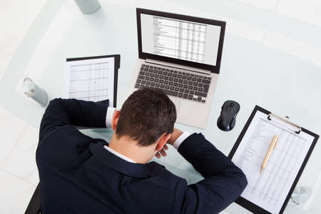 High angle view of tired businessman sleeping while calculating expenses at desk in office photo