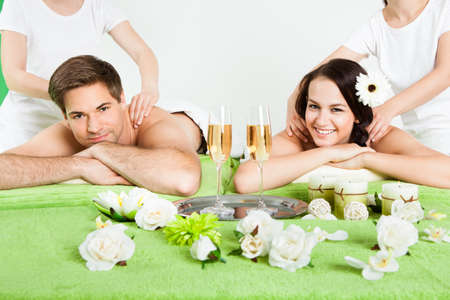 Portrait of happy young couple receiving shoulder massage at beauty spa photo