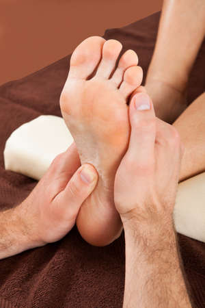 foot cream: Closeup of male therapist giving foot massage to female customer at beauty spa