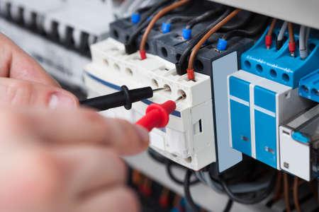 Close-up van mannelijke elektricien onderzoeken zekeringkast met multimeter probe