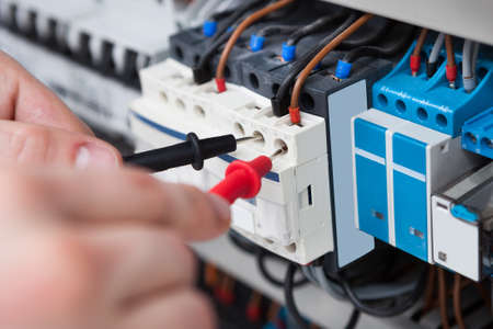 ingeniero: El primer del varón electricista examinar la caja de fusibles con sonda multímetro Foto de archivo