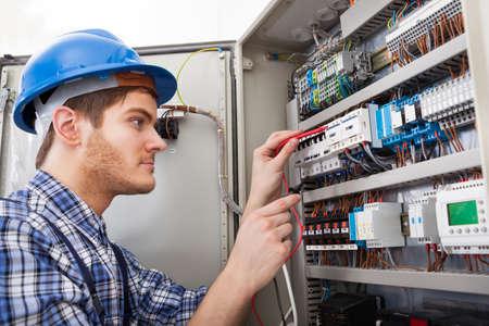 ingeniero electrico: Vista lateral de la caja de fusibles masculino técnico que examina con el multímetro
