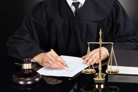 Midsection of male judge writing on paper at desk against black background photo
