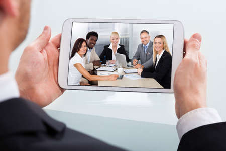 conferencing: Cropped image of businessman video conferencing on digital tablet at desk in office