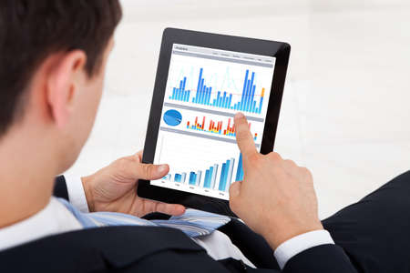 Midsection of young businessman comparing graphs on digital tablet in office photo