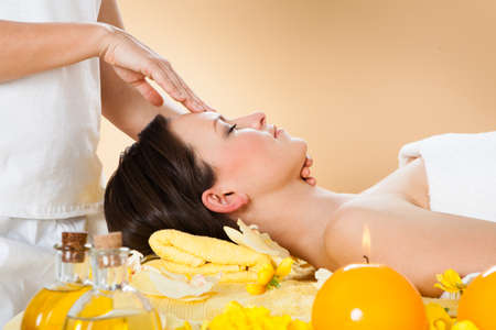 Side view of young woman receiving head massage in spa photo