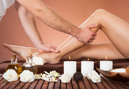 foot cream: Cropped image of male therapist massaging female customers leg at beauty spa Stock Photo