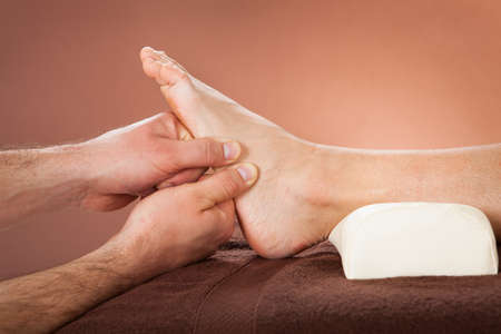 color therapist: Cropped image of male therapist giving foot massage to female customer at beauty spa