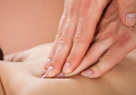 fisioterapia: Primer plano de la terapeuta masculino masajear la espalda de los clientes de sexo femenino en el spa de belleza