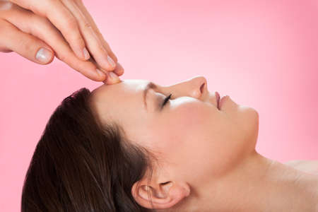 color therapist: Side view of young woman receiving head massage in spa Stock Photo