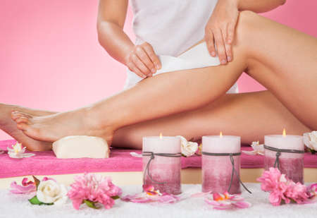 beauty therapist: Midsection of female therapist waxing customers leg at beauty spa