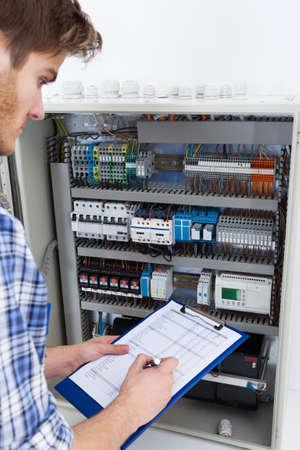 ingeniero electrico: Recorta la imagen de técnico de los hombres la celebración portapapeles mientras examina la caja de fusibles Foto de archivo