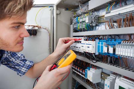 fusebox: Side view of male technician examining fusebox with digital insulation resistance tester