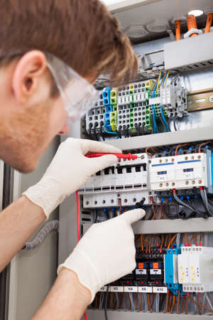 fusebox: Cropped image of male electrical engineer examining fusebox with multimeter probe Stock Photo