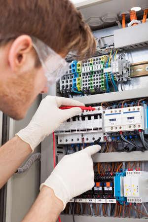 electricista: Recorta la imagen de macho ingeniero el�ctrico caja de fusibles que examina con el mult�metro Foto de archivo