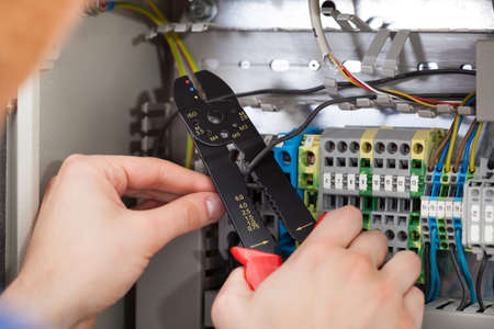 box cutter: Closeup of male technician cutting cable with fusebox in background