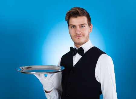Portrait of confident waiter carrying tray over blue background photo