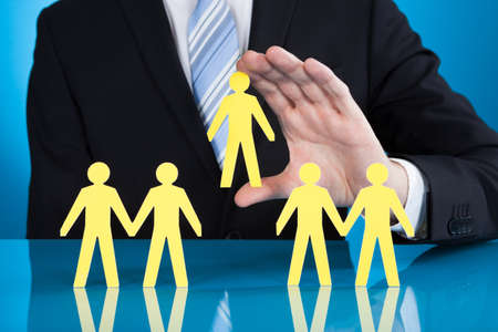cut the competition: Midsection of businessman holding paper people representing recruitment against black background