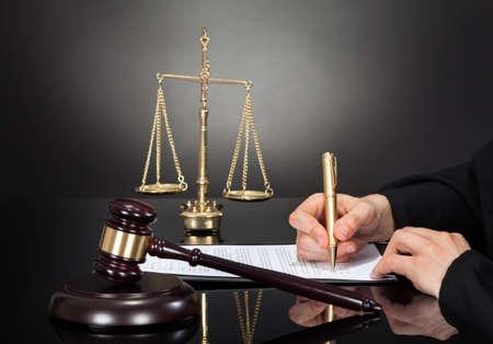 Freigestellte Bild von männlichen Richter Dokument signieren am Schreibtisch vor schwarzem Hintergrund