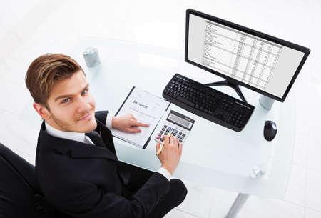 Hoge hoek mening van zakenman het berekenen van de kosten bij de balie in kantoor