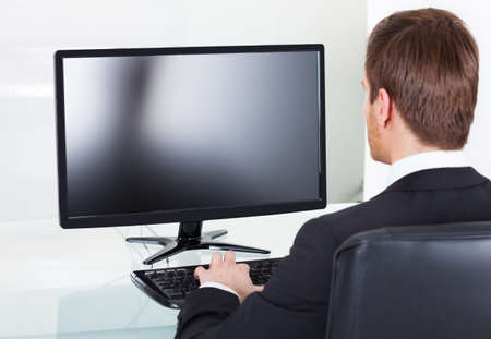 rear views: Rear view of young businessman using computer at desk in office