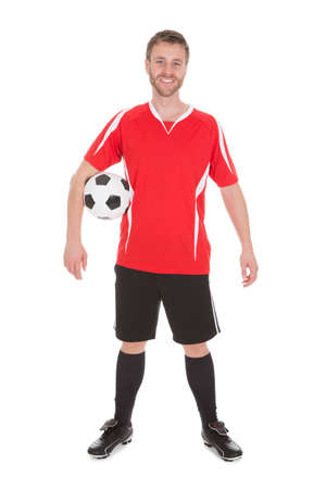 sportsperson: Portrait of young soccer player holding football over white background