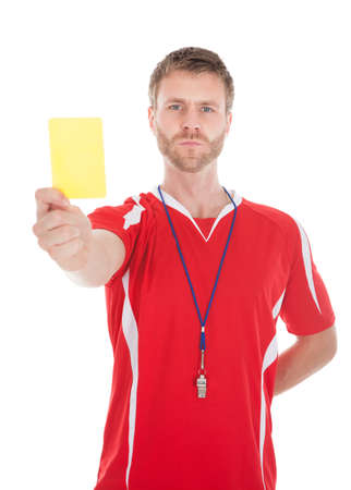 Portrait of referee blowing whistle while showing yellow card over white background photo