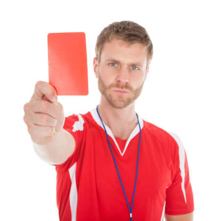 Full length portrait of referee showing red card over white background photo
