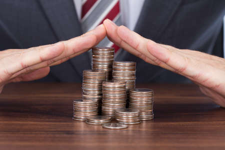sheltering: Midsection of businessman sheltering coin stacks on table