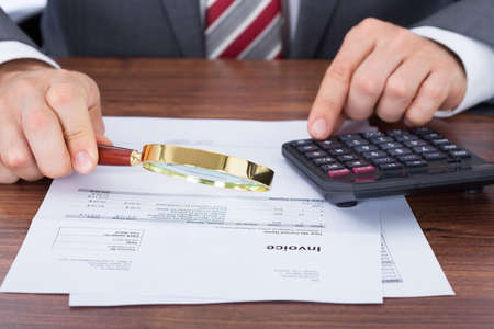 Midsection of businessman calculating invoice while holding magnifying glass at desk photo