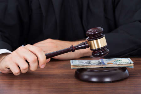 Midsection of male judge striking gavel on banknotes at desk in courtroom photo