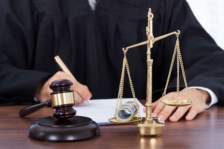 Midsection of male judge signing document with mallet and scale on desk