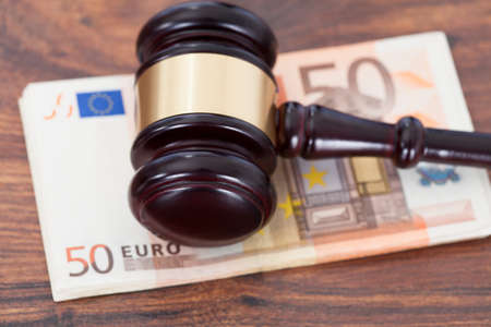 Closeup of judge mallet over euro banknotes on table photo