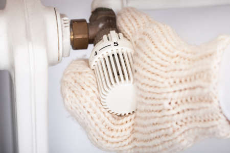 thermostat: Closeup of hand wearing mitten turning knob of radiator