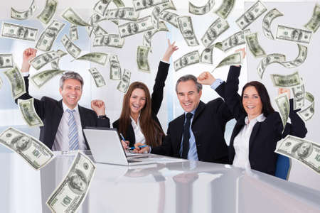 Portrait of successful business people with money rain in conference room photo